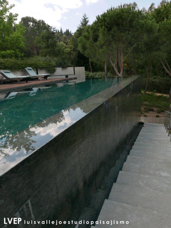 Piscina desbordante, vaso y muro desbordante, chapado en granito negro encina, jardín privado (Madrid)