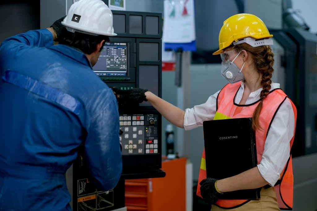 Factory worker woman with mask point to the monitor of machine with engineer man